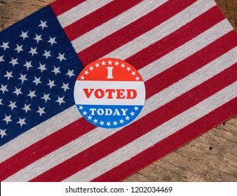 I Voted Today sticker  for voters in the US elections with USA flag on rustic wooden table