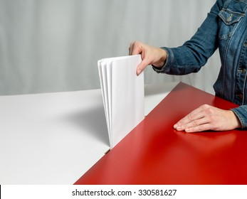 Voter casting a vote into ballot box during election to the Polish Parliament