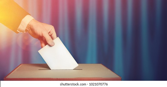 Voter Holds Envelope In Hand Above Vote Ballot Blue Surface. Freedom Democracy Concept