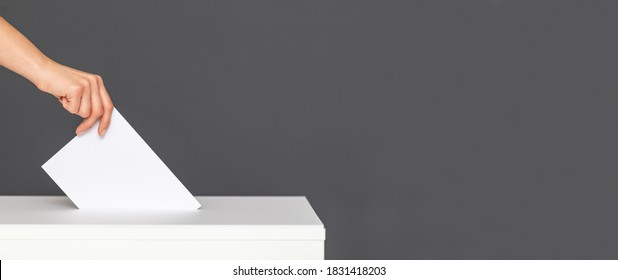 The voter holds his vote ballot paper and places it in the ballot box. Filling in ballots and casting votes in booths at polling station.The concept of free democratic vote elections.