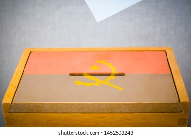 A voting box with the flag of Angola and white voting paper
