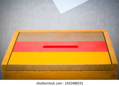 A voting box with the flag of Germany and white voting paper