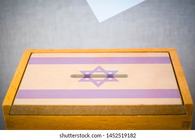 A voting box with the flag of Israel and white voting paper