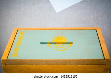 A voting box with the flag of Kazakhstan and white voting paper