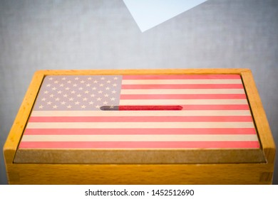 A voting box with the flag of US and white voting paper