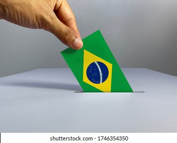 Voting / election concept: hand holding voting card with country national flag, inserting it into white ballot box; clean neutral background — Brazil