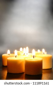 Votive candles burning with a soft glow flame with smoke above for meditation or relaxation in peaceful mood and soft ambiance