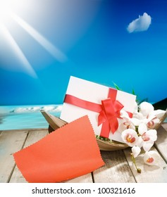 Voucher in a palm bowl with a bow at a deck in front of the deep blue pacific ocean and a shiny sun. With copyspace for your own Text and messages