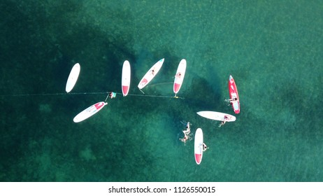Vouliagmeni, Attica / Greece - July 03 2018: Aerial drone photo of Sup (Stand Up Paddle) Yoga lesson