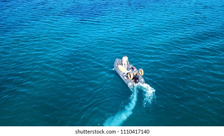 Vouliagmeni, Attica / Greece - June 08 2018: Aerial bird's eye view of inflatable rib boat cruising in high speed in turquoise clear water sea
