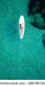Vouliagmeni, Attica / Greece - May 09 2018: Aerial photo of man practising paddle surfing or sup in clear waters of Vouliagmeni beach
