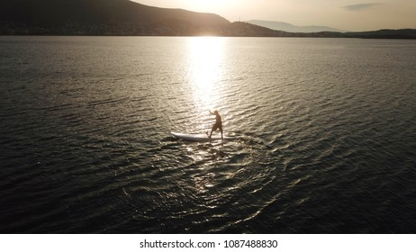 Vouliagmeni, Attica / Greece - May 09 2018: Aerial photo of man practising paddle surfing or sup in clear waters of Vouliagmeni beach at sunset