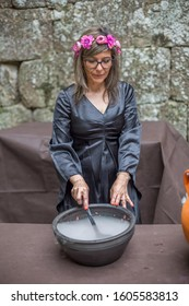Vouzela / Portugal - 07 07 2019 : View of a witch performing in medieval market, actress dressed in witch's robes and cooking magic potion