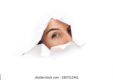 Voyeurism. A curious female look. Spying on or overhearing the concept. Hole on White paper.