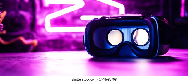 VR 3d 360 headset glasses goggles in futuristic purple neon light on table desk, virtual augmented ar reality innovative experience digital technology background concept, copy space wide photo banner
