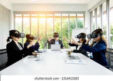 VR Business People wearing virtual reality with touching air during VR Meeting Conference at the office. Business man and women using VR goggles in meeting room.