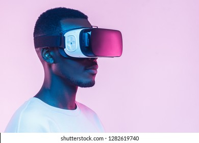 VR concept. Young african man wearing  virtual reality goggles, isolated on pink background