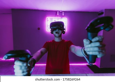 VR E-Sports. The guy is playing an online shooter in the game neon room. High quality photo