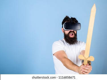 VR gamer concept. Guy with head mounted display and sword play fighting game in VR. Hipster on shouting face enjoy play game in virtual reality. Man with beard in VR glasses, light blue background.