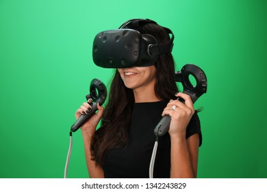 VR girl playing with virtual relaity headset isolated on green screen background. Virtual Reality emotions by games for Black hair young girl