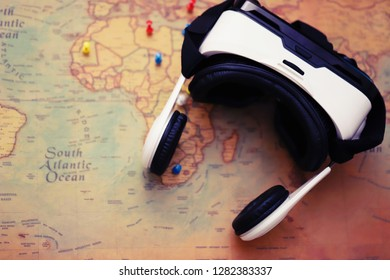 VR glasses on a world map with pushpins. Virtual reality travel experience concept.