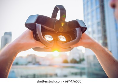 VR Goggles in male hands. Man ready to wear virtual reality goggles. The vr headset design is generic and no logos. Backward light, selective focus, close up. Sunset city landscape