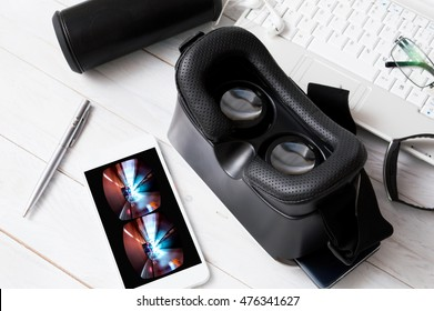 VR ocular and smartphone with VR car game lying on white wooden desk