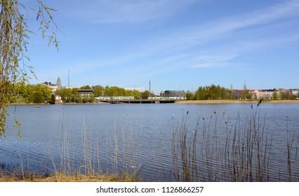 VR Pendolino trains cross a bridge on the far side of Toolo bay in Helsinki City Park