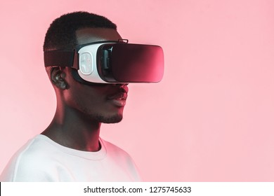 VR technology. Young african man wearing virtual reality headset, isolated on pink background