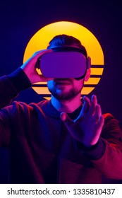 VR videogame experience in 80's synthwave and retrowave futuristic aesthetics. Man wearing virtual reality goggles wireless headset and interacting with hand gestures.
