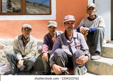 Vrang, Tajikistan August 24 2018: Four older men are sitting on the stairs in front of the Bibi Fatima hot springs in Wakhan valley in Tajikistan