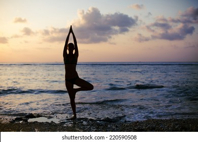 Vrikshasana tree pose from yoga by woman silhouette on sunset
