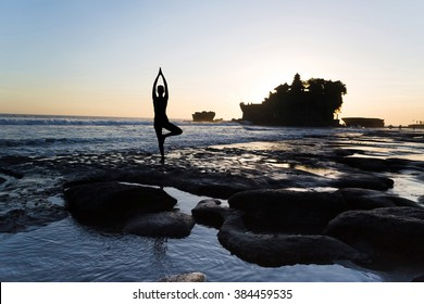 Vrikshasana tree pose from yoga by woman silhouette on sunset near Tanah lot temple