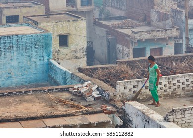 Vrindavan, 22 October 2016: A woman cleaning the roof, in Vrindavan, UP