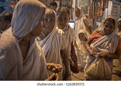 Vrindavan, India, August 2009. Widows in the street next to the entrance of an ashram at night.
