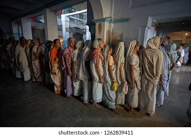 Vrindavan, India, August 2009. Widows standing in line inside an ashram to eat.