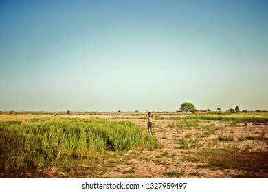 Vrindavan, India - Jul 2018: Unidentified Indian rural boy in the field and playing at morning, an Indian rural scene.