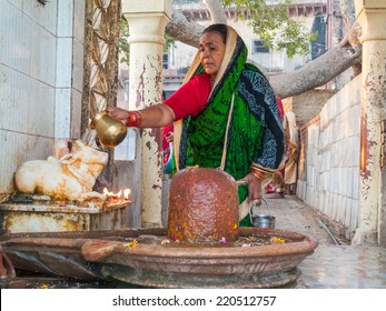 VRINDAVAN, INDIA - OCT 10th - A Hindu woman worships a Shiva linga in a shrine in Vrindavana, India on October 10th, 2009