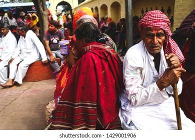 Vrindavan, Uttar Pradesh / India - February 27 2017 : Old man sitting beside his wife in Vrindavan temple during Holi