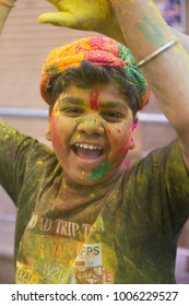 VRINDAVAN, UTTAR PRADESH, INDIA - MARCH 12, 2017: Portrait of unidentified Hindu boy traditionally covered with colorful powder, celebrating Holi festival in the streets of Vrindavan, India