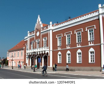 VRSAC, SERBIA; 25. JULY 2009. People walk in front of the Vrsac City Hall. The building was built in a neo-gothic style in the 19th century.
