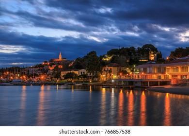 VRSAR, CROATIA - NOVEMBER 1st 2017: Lights of the Croatian coast town Vrsar reflecting in the adriatic sea at dawn
