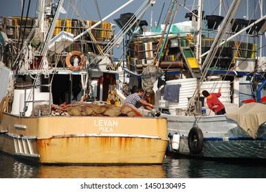 Vrsar, Croatia - Otober 3 2007: Men working on fishing boats in harbor of Vrsar in Croatia