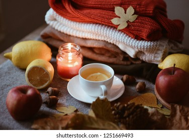 VSCO with a4 preset. Autumn leaves,candles on wooden background. Autumn or Winter concept. Autumn composition. Cup of tea with lemon, leaves, lemons, apples, burning candle, sweaters, acorns. Flatlay.