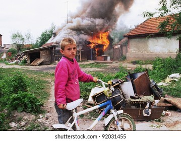 VUCITRN, KOSOVO - JUNE 26: A young ethnic Serb boy watches his house burn to the ground in Vucitrn, Kosovo, on Saturday, June 26, 1999. Ethnic Albanians burned ethnic Serb houses after NATO peacekeepers entered the province.