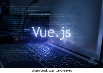 Vue.js inscription against laptop and code background. Learn vue programming language, computer courses, training.