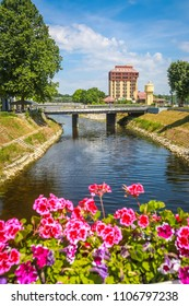 VUKOVAR, CROATIA - MAY 14, 2018 : View of flowers and pedestrian bridge of Jean Michel Nicolier with abandoned hotel Dunav in the background in Vukovar, Croatia.