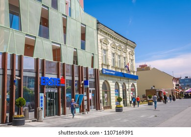 VUKOVAR, CROATIA - MAY 14, 2018 : People walking in the city center in front of the Erste bank building in Vukovar, Croatia.