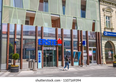 VUKOVAR, CROATIA - MAY 14, 2018 : A young woman walking in front of the Erste bank building in Vukovar, Croatia.