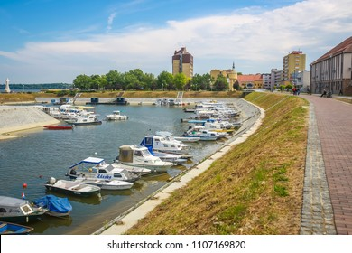 VUKOVAR, CROATIA - MAY 14, 2018 : A view of boats moored on the coast of the river Dunav with people walking on the promenade and the Hotel Dunav in the background in Vukovar, Croatia.